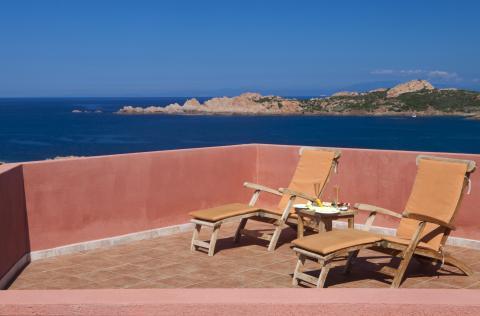 Balkon met ligstoelen en uitzicht.